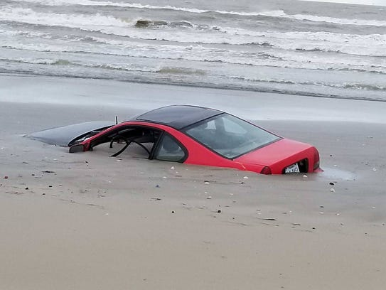 A red Honda Prelude was buried in the sand at the beach