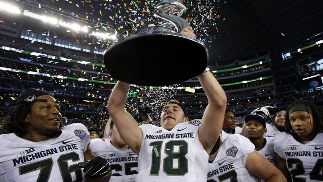 Quarterback Connor Cook holds up the Cotton Bowl trophy after MSU's 42-41 win over Baylor on Jan. 1. Cook and the Spartans enter the 2015 season ranked No. 5 in the AP preseason poll.