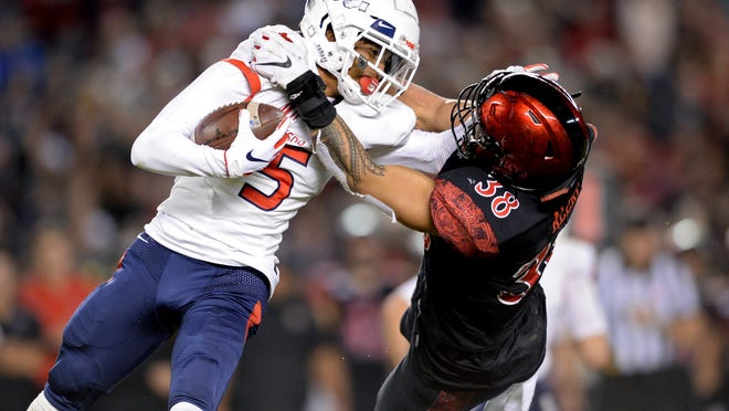Fresno State wide receiver Jalen Cropper, left, is tackled by San Diego State linebacker Andrew Aleki during the first half of the NCAA college football game Friday, Nov. 15, 2019, in San Diego. (AP Photo/Orlando Ramirez)