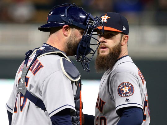 Houston Astros catcher Brian McCann, left, chats with pitcher Dallas Keuchel after Keuchel gave up a walk to Minnesota Twins' Brian Dozier to load the bases during the second inning of a baseball game Tuesday, April 10, 2018, in Minneapolis. (AP Photo/Jim Mone)