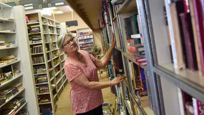 Grapevine Books owner Nina Jackson rearranges some of the Gallatin bookstore's collection Wednesday, Oct. 12. The North Water Avenue business will close later this year after nearly 17 years.