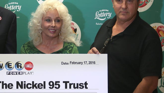 Florida Lottery Secretary Tom Delacenserie, left, presents Maureen Smith and David Kaltschmidt with their one-third share of the Jan. 13, world record Powerball jackpot.