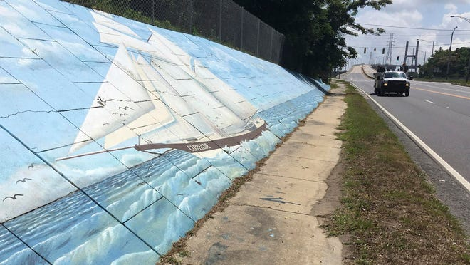 Traffic passes a mural of the slave ship Clotilda along Africatown Boulevard in Mobile, Ala.