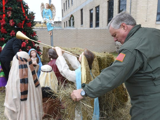 Local attorney Rick Spencer works Thursday morning putting up a nativity scene at the Baxter County Courthouse. Spencer has been erecting the religious display for years in honor of his late wife.