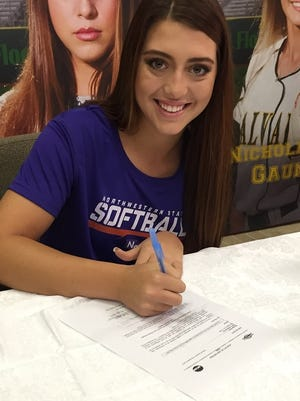 Calvary's Marissa Reed signs scholarship papers with Northwestern State.