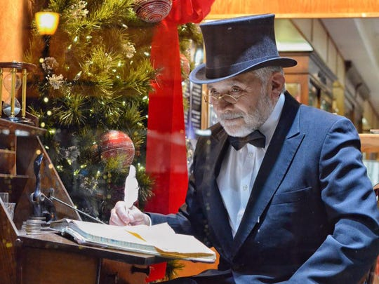 "Ebenezer Scrooge writes at his desk in a ""Living Windows"""