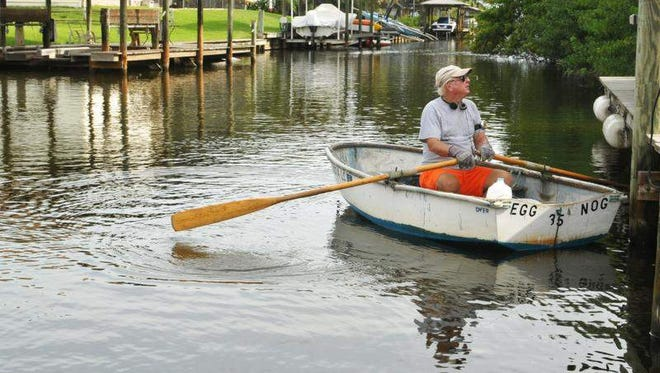 Owen McElroy rows along a canal often plagued by shallow water. Residents in Indian River Isles near Rockledge have trouble operating their powerboats in the muck-filled canals.