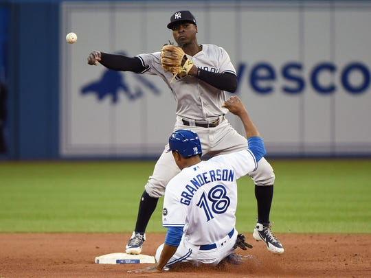 New York Yankees shortstop Didi Gregorius (18) throws to first for a double play after forcing out Toronto Blue Jays right fielder Curtis Granderson (18) at second base in the sixth inning at Rogers Centre.