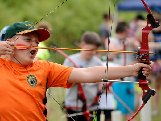 Spencer Hauck tries his hand at archery Saturday at Outdoor University at the Outdoor Campus, Aug 2, 2014.