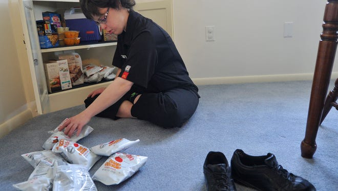 Sarah Keeney unpacks her snacks on her first day in her new group home, on Saturday, Feb. 27, 2016. Keeney, who has special needs and can't live totally independently, was living with her mother Suzanne Keim. She had applied for a consolidated waiver from the state which helped her to be able to move into the group home with two of her longtime friends.