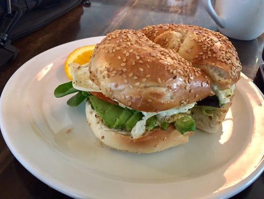 A Bagel Sandwich with a fried egg, greens, avocado
