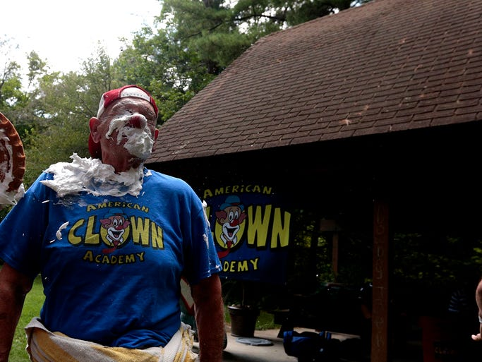 James W. Long has a pie thrown in face by ------------- as part of a pie throwing demo at The America Clown Academy. Students from across the country are learning trade clown secrets this week, including how to make pies and throw them.