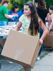Sienna Nanni, 9, carries a box of books during Vineland School District's book giveaway at the Vineland School District Warehouse on Wednesday, August 30.