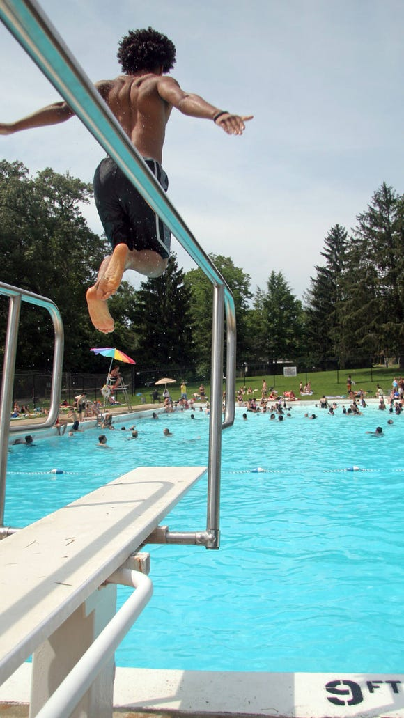A swimmer prepares to jump into the Malvern Hills pool in West Asheville in this file photo. City pools will start to open Memorial Day.