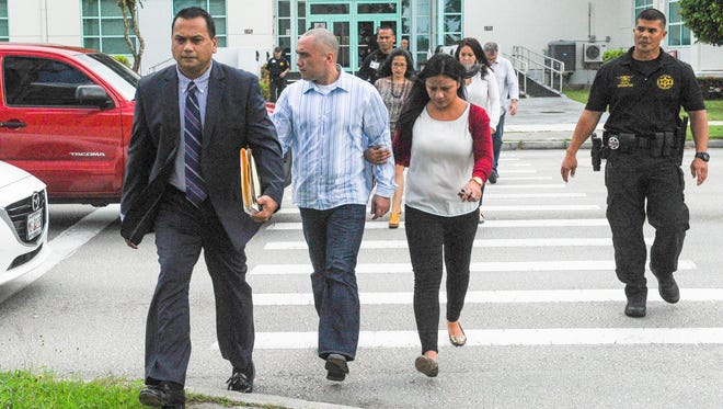 Mark Torre Jr., center, crosses the street with his attorney, Jay Arriola, left, and others after a preliminary hearing at the Guam Judicial Center in Hagatna on July 24.