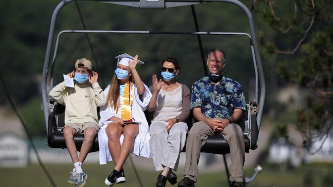 Kennett High School graduate Helen Badger waves while riding with family members on a ski chairlift to the summit of Cranmore Mountain Resort to receive his diploma, Saturday, June 13, 2020, in North Conway. The school came up with a unique commencement ceremony in order to adhere to the social-distancing guidelines necessitated by the coronavirus pandemic.