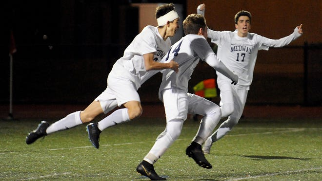Medway's Troy Newman (center) is congratulated by Danny MacDonald (right) and Kyle Myers after scoring the winning goal against Bedford to win the Div. 3 state semifinals last fall at Manning Field in Lynn. Newman is a senior on this fall's Medway team.