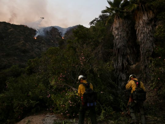 Members of hand crew cut down tress as a firefighting helicopter making a water drop on a wildfire in Duarte, Calif., Tuesday, June 21, 2016.