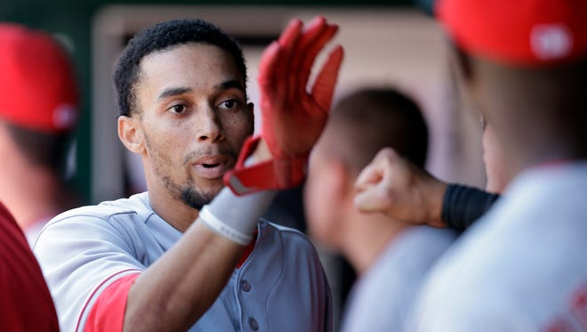 Cincinnati Reds' Billy Hamilton is congratulated by teammates in the dugout after scoring on a single by Brandon Phillips during the ninth inning.