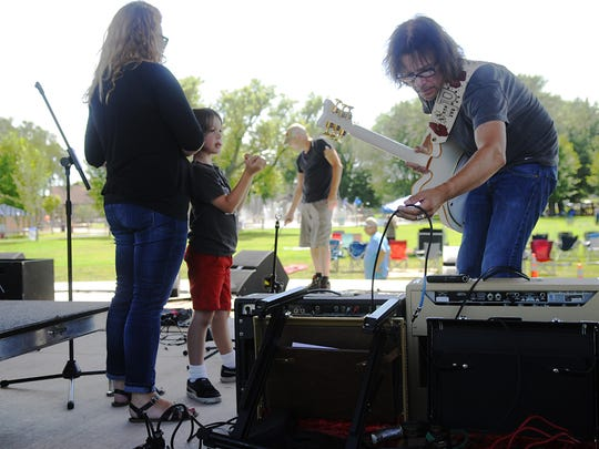 G.B. Leighton lead guitarist Patrik Tanner sets up his equipment for Summertime by George! while his wife, Michelle, and his son, Elliott, watch on July 22 at Lake George.
