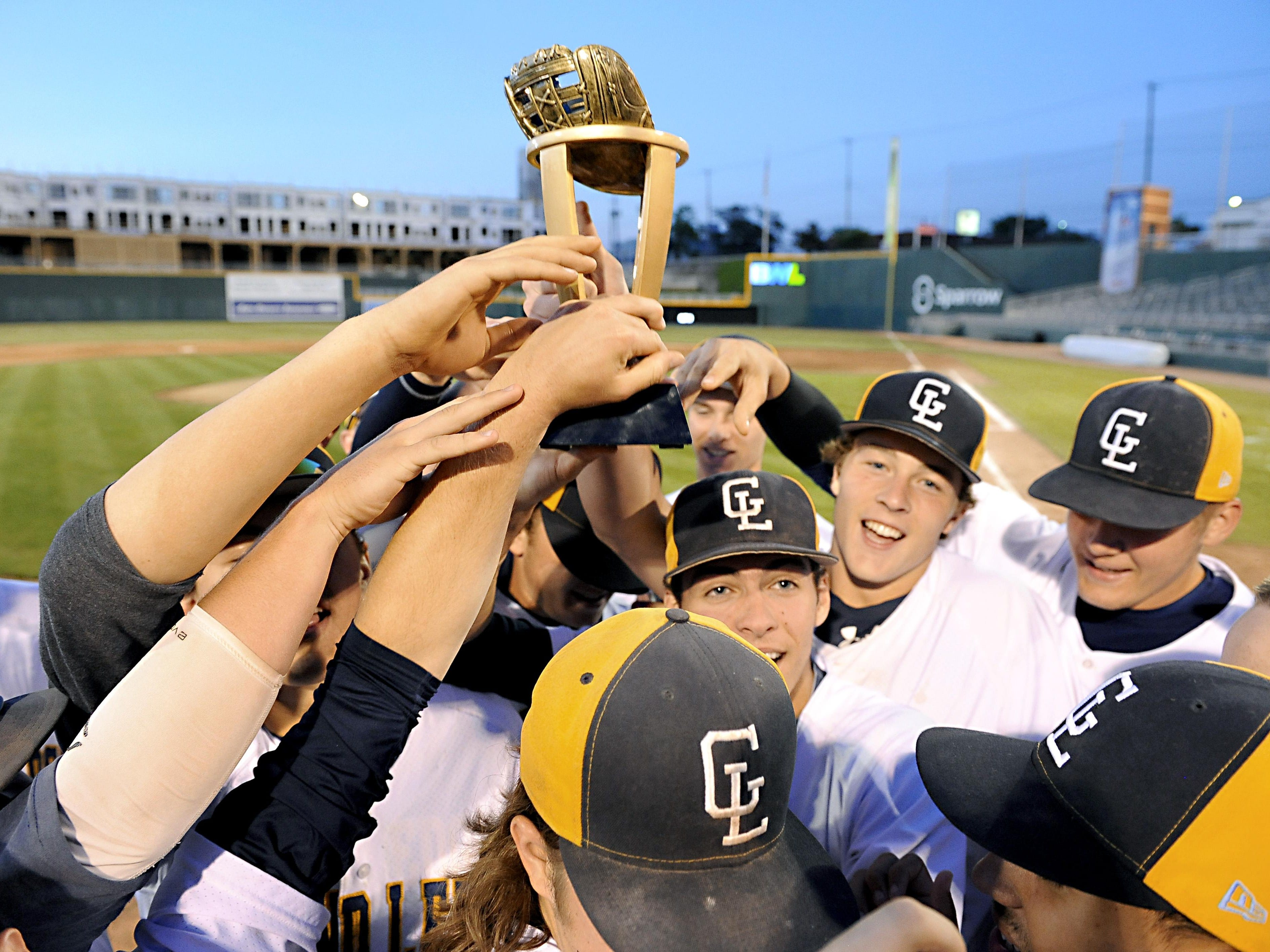 The Grand Ledge Comets hold up the Diamond Classic Championship trophy after the Comets' 4-1 win over St. Johns in the championship game Tuesday.
