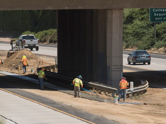 Construction crews pour concrete foundations on Tuesday, May 23, 2017 for new guard railings between eastbound and westbound traffic on Highway 198 between County Center and Akers Road.