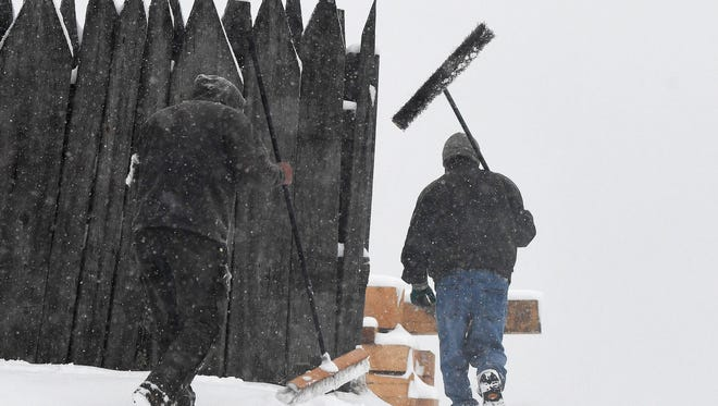 Large brooms are carried after they were used to brush the snow from vehicles at Blue Ridge Lumber Co. in Fishersville on Monday, March 12, 2018.