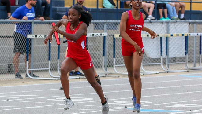 Pine Forest's Gabrielle Fountain takes off running the second leg of the 4x400m relay after teammate Nicosha Nobles in the Andrews Invitational at Gulf Breeze High School on Thursday, March 29, 2018.