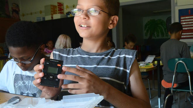 Fremont Elementary School fourth-grader Dante Hartzell, 9, shows off the Walking Classroom WalkKit he helped to unwrap during class Friday.