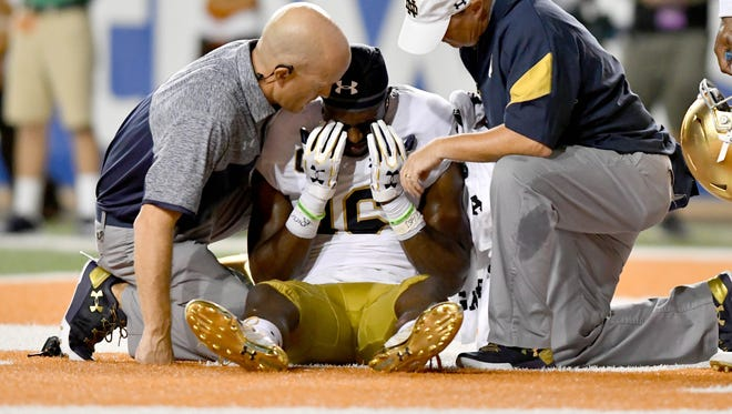 Notre Dame Fighting Irish wide receiver Torii Hunter Jr. is tended to by medical staff after a hard hit in the third quarter against  Texas. No targeting was called, but the hit certainly was controversial.