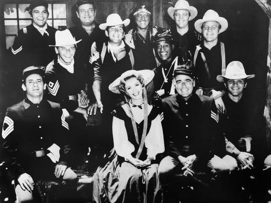 "A photo of the cast from ""Sergeants 3"" with Actress Ruta Lee at the center surrounded by the Rat Pack."