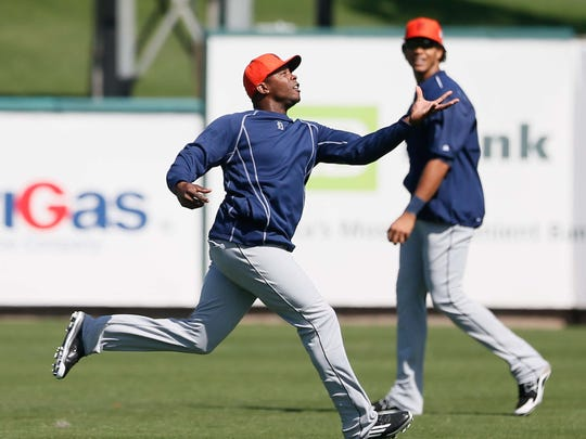 Tigers outfielder Justin Upton runs to catch a ball with his bare hand for a drill, while Steven Moya looks on during spring training at Joker Marchant Stadium on Feb. 25.