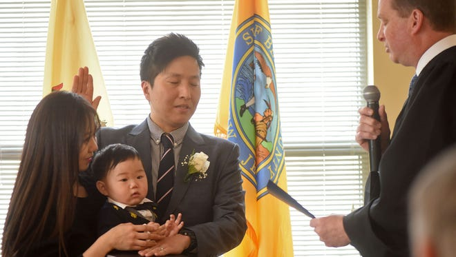Steve Chong is sworn in as deputy clerk for Bergen County by Superior Court Judge James X. Sattely on Wednesday, March 14, 2018. With him are his wife, Sinae, and son Bryce.