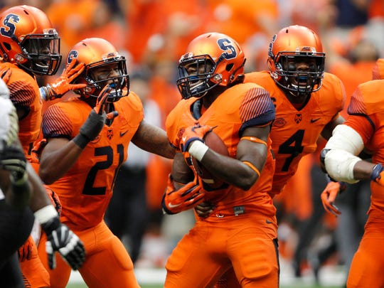 Syracuse's Parris Bennett, center, celebrates with teammates after catching an interception in the first quarter of an NCAA college football game against Wake Forest in Syracuse, N.Y., Saturday, Sept. 12, 2015. (AP Photo/Nick Lisi)