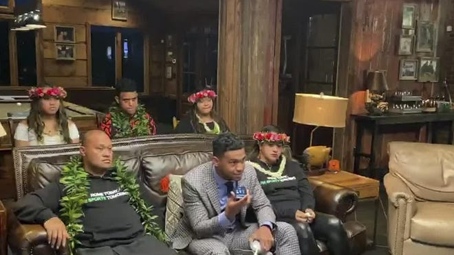In this still image from video provided by the NFL, Tua Tagovailoa, front center, holds up a phone during the NFL Draft. The Dolphins selected Tagovailoa with the fifth pick.