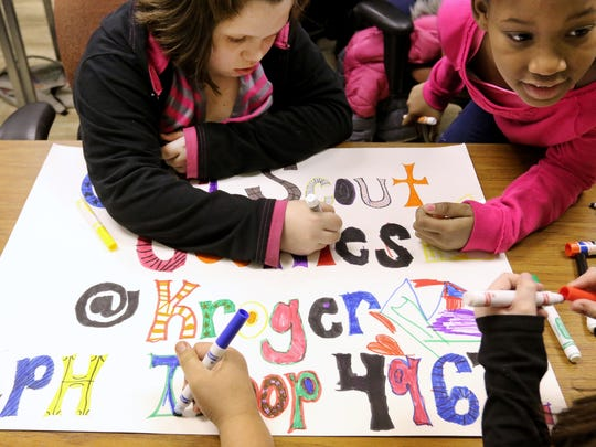 Troop 49632 members Adrianna Daniels, 9, and Eumayah Solomon, 9, work on a poster they'll have on display when they start selling Girl Scout cookies in March.