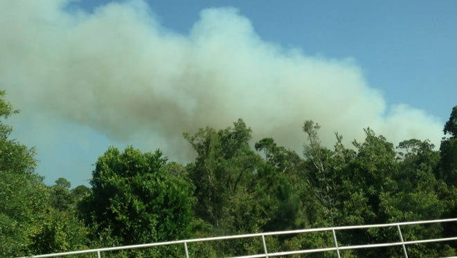 Smoke from a brush fire in the Naval Live Oaks area of Gulf Breeze