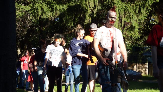 Zombies stroll through Iowa City on Saturday, Sept. 12, 2015, as part of the 10th annual Zombie March.