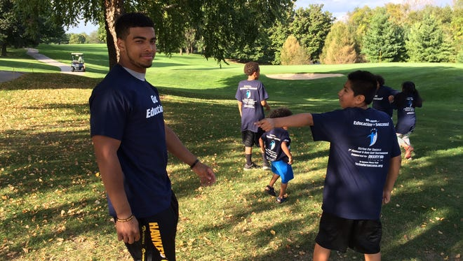 Hawkeye running back Jordan Canzeri tosses a football around with students enrolled in the Strive for Success program at the organization's first annual Nine Hole Golf Tournament on Sunday.