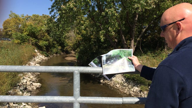 Doug Ollendike, community development director in Clive, shows a before picture of erosion management efforts along Walnut Creek.