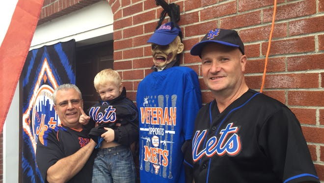 From left, Mike Francavilla, Max Becker and Hugh Becker show off their enthusiasm over the Mets advancing to the World Series outside of the Beckers' home in Hillcrest.