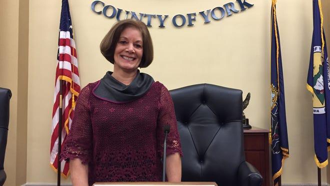 Susan Byrnes stands behind her new President Commissioner nameplate.