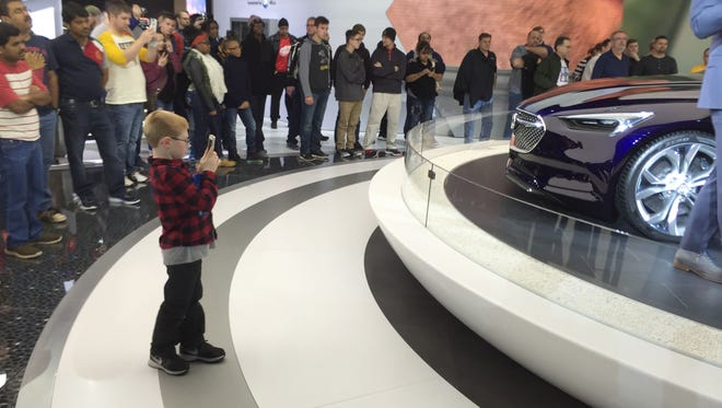 Mason Strozik, 6, snaps pictures of the Buick Avista concept car at the North American International Auto Show Saturday, Jan. 16, 2016, at Cobo Center in downtown Detroit.