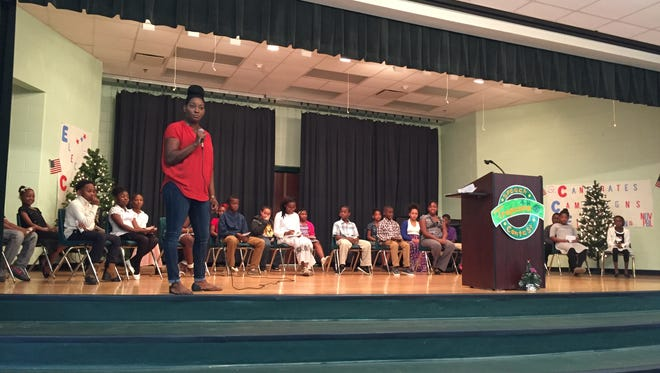 Bond Elementary reading coach Latoyer Hankerson welcomes the audience to the school's speech competition in December.