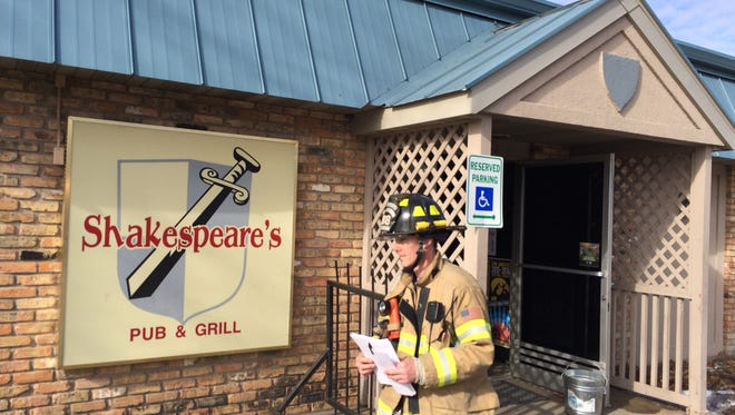A firefighter leaves Shakespeare's Pub and Grill on Thursday morning after crews extinguished a fire that started in the kitchen.
