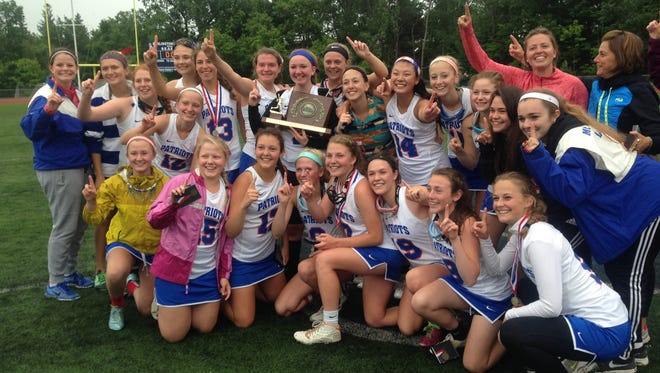 The Mount Anthony girls lacrosse team celebrates the Division I state title on Saturday at Burlington High School.