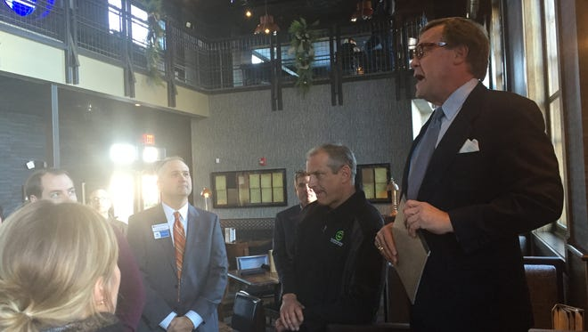 Marsh Davis (left), president of Indiana Landmarks, speaks at the official opening of Bru Burger Bar Monday in the former Greyhound station in Downtown Evansville.