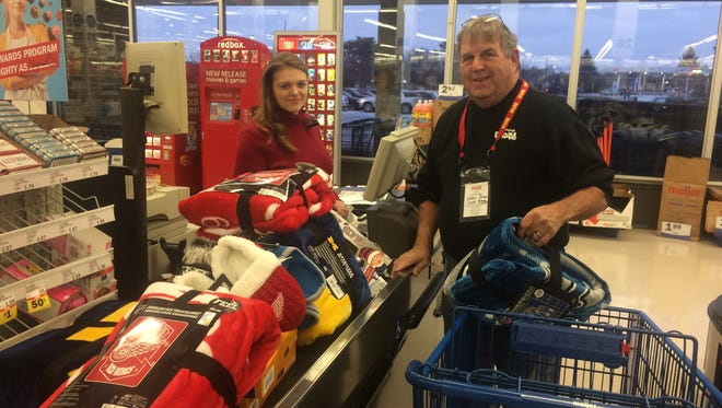 Meijer employee Megan Williams helps Toys for Tots coordinator Gary Dunn during the holiday shopping event at the store.