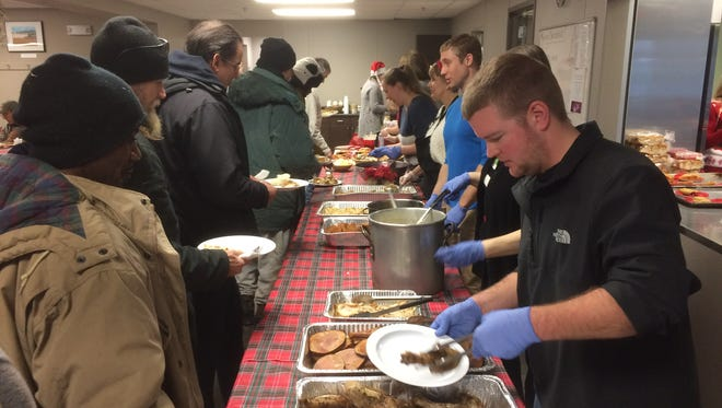 Volunteer Tim Lipsius, right, serves food at the Free Lunch Program's annual Christmas Day meal on Sunday.