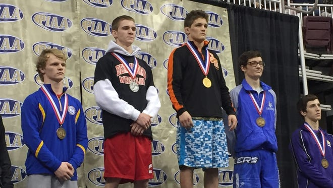 Bermudian Springs senior Austin Clabaugh (second from left) stands on the podium with his silver medal around his neck after losing in the PIAA Class 2-A 126-pound championship bout to Jefferson Morgan's Gavin Teasdale, 13-5.